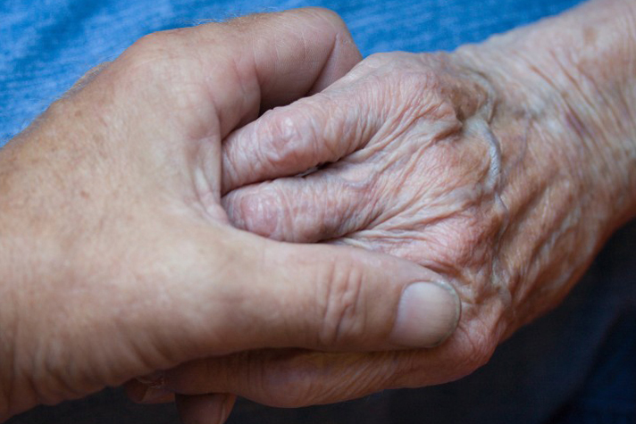 elderly woman holds son's hand