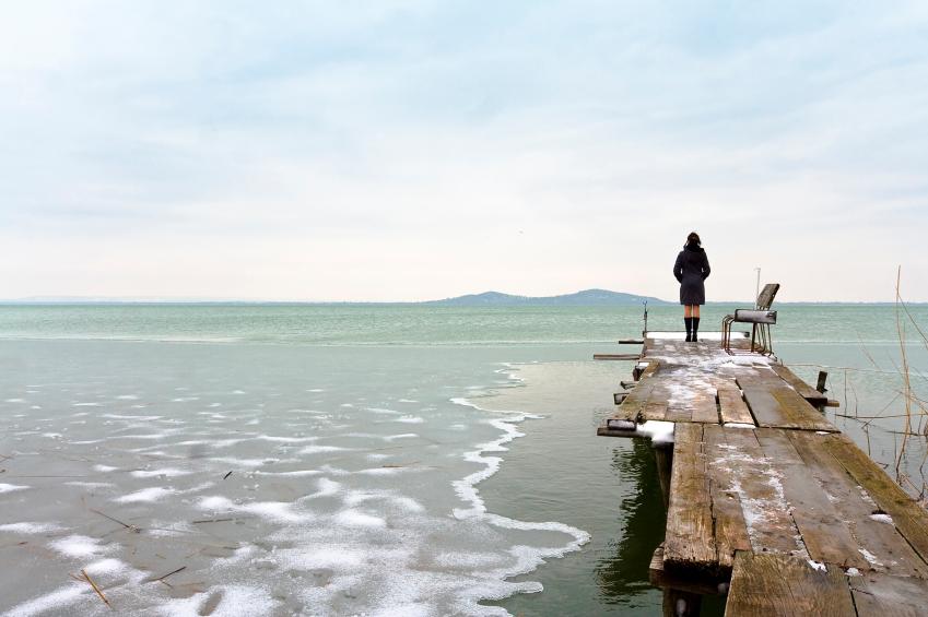 woman on pier looking at ocean