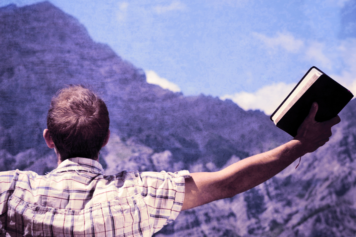 man's arms open with Bible