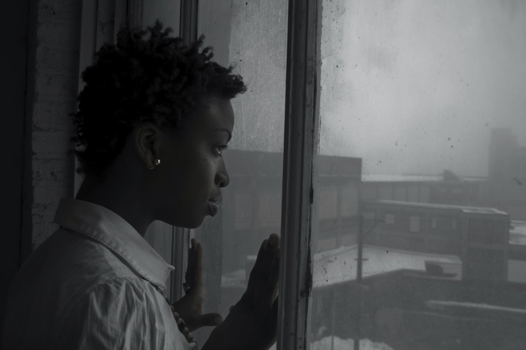 woman looking out window on dark day