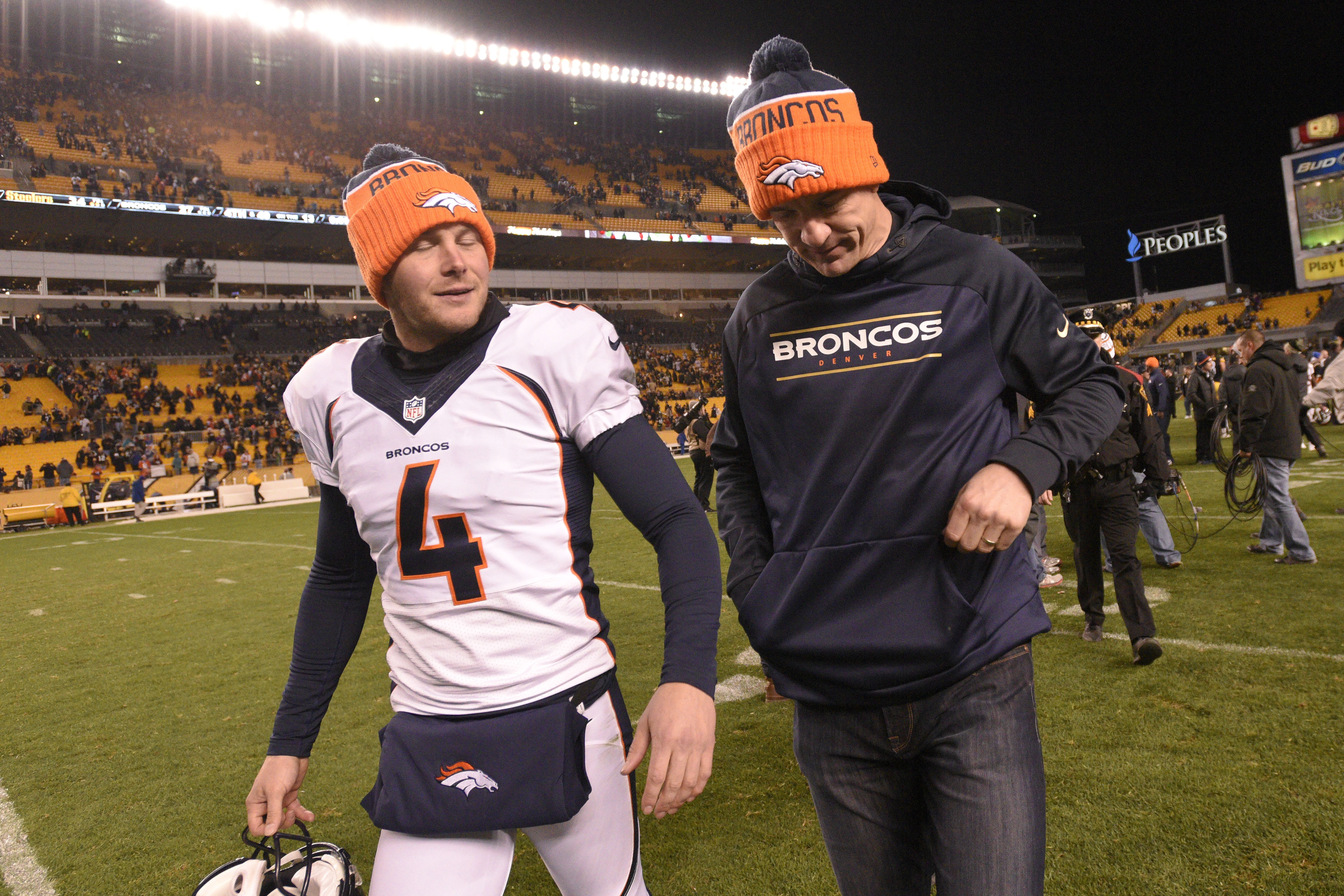 Denver Broncos punter Britton Colquitt (4) and quarterback Peyton Manning (18) leave the field after an NFL football game against the Pittsburgh Steelers, Sunday, Dec. 20, 2015, in Pittsburgh. The Steelers won 34-27. (AP Photo/Don Wright)
