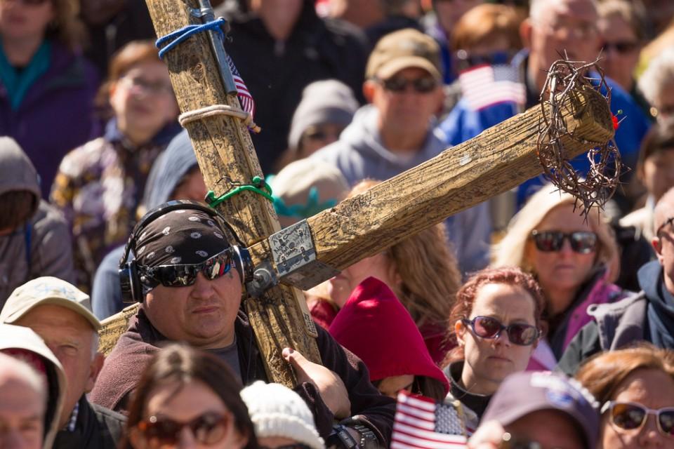 Man holding wooden cross