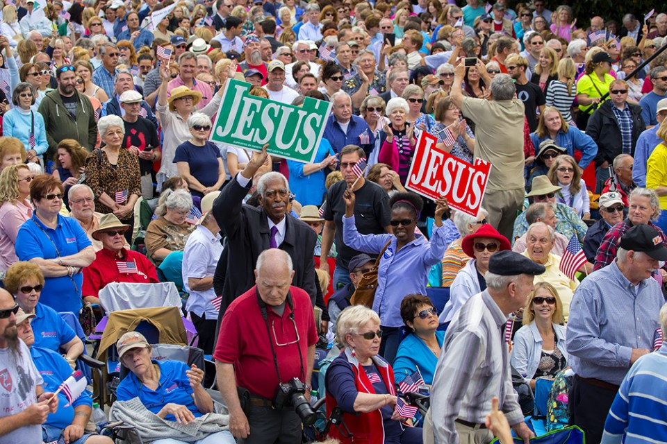 "Man and woman holding ""Jesus"" signs"