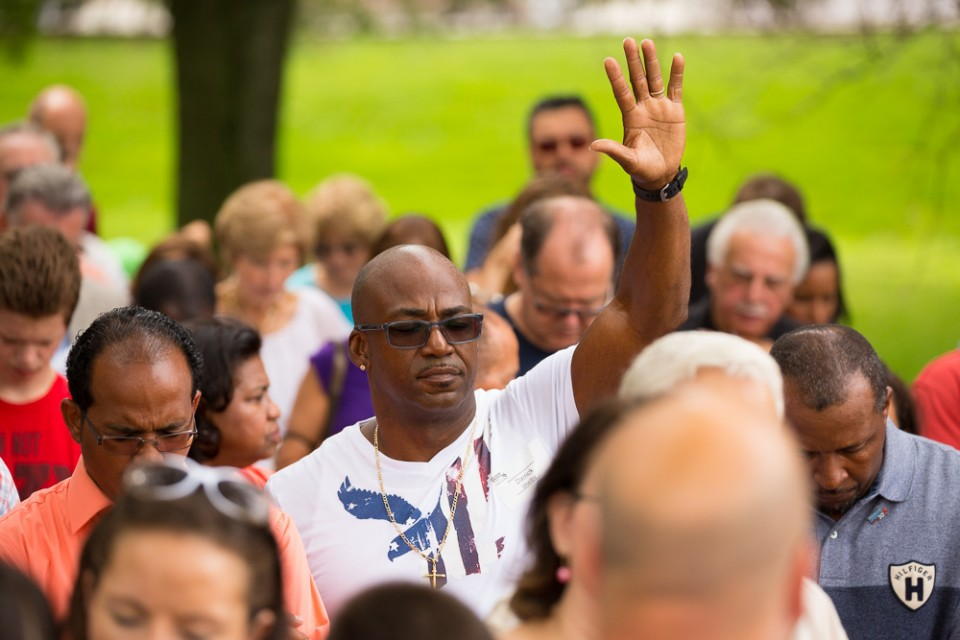 Man with USA t-shirt in crowd. Lifting hand to God