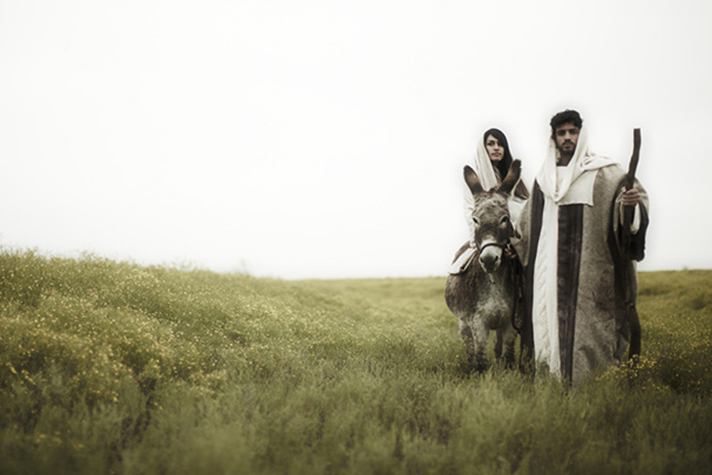 Joseph leading Mary on a donkey in field