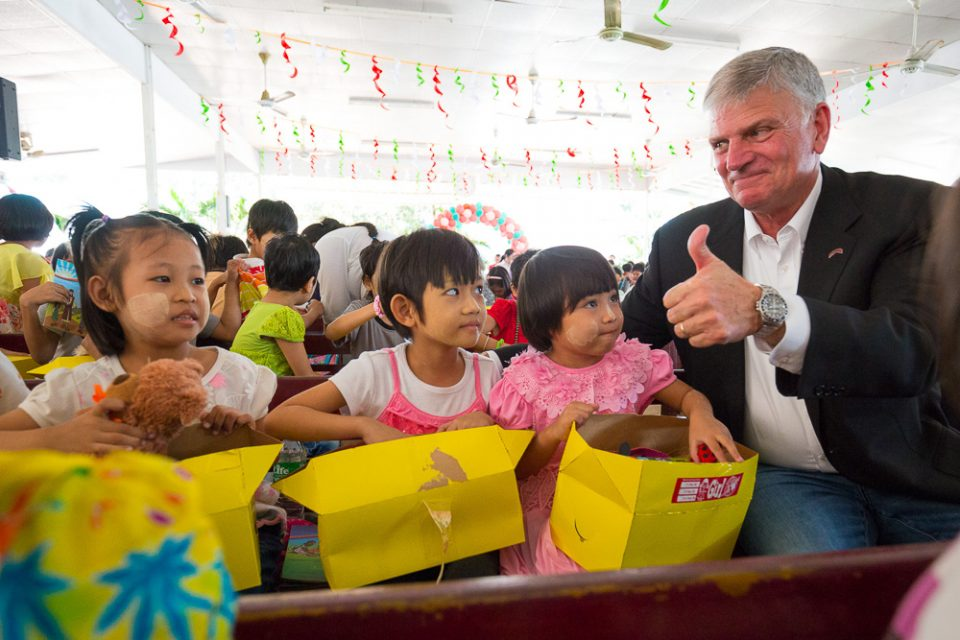 Franklin Graham gives thumbs up; three children opening gift-filled shoeboxes
