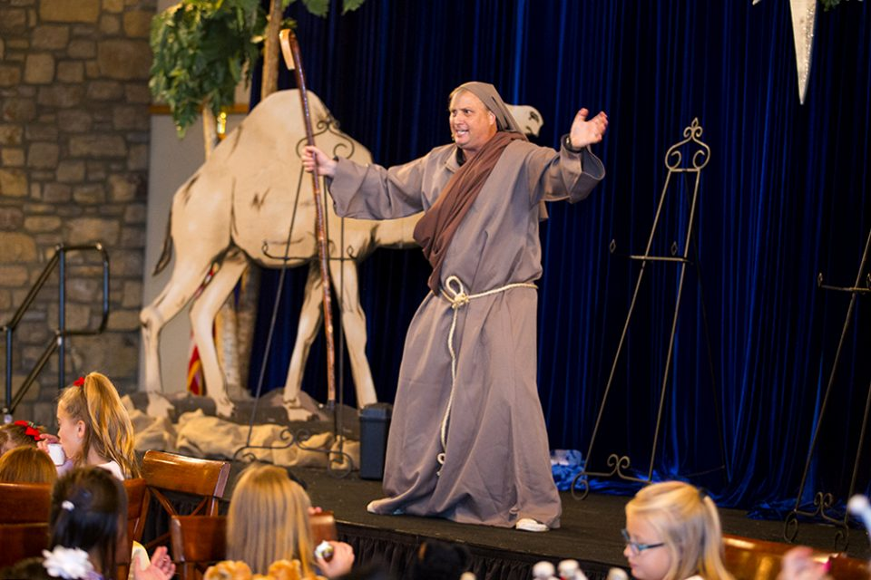 Children's entertainer Ted Loring dressed in shephard outfit and holding staff on stage