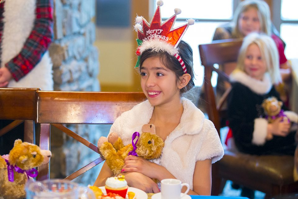 Girl smiling and holding stuffed camel; wearing 'Merry Christmas' headband