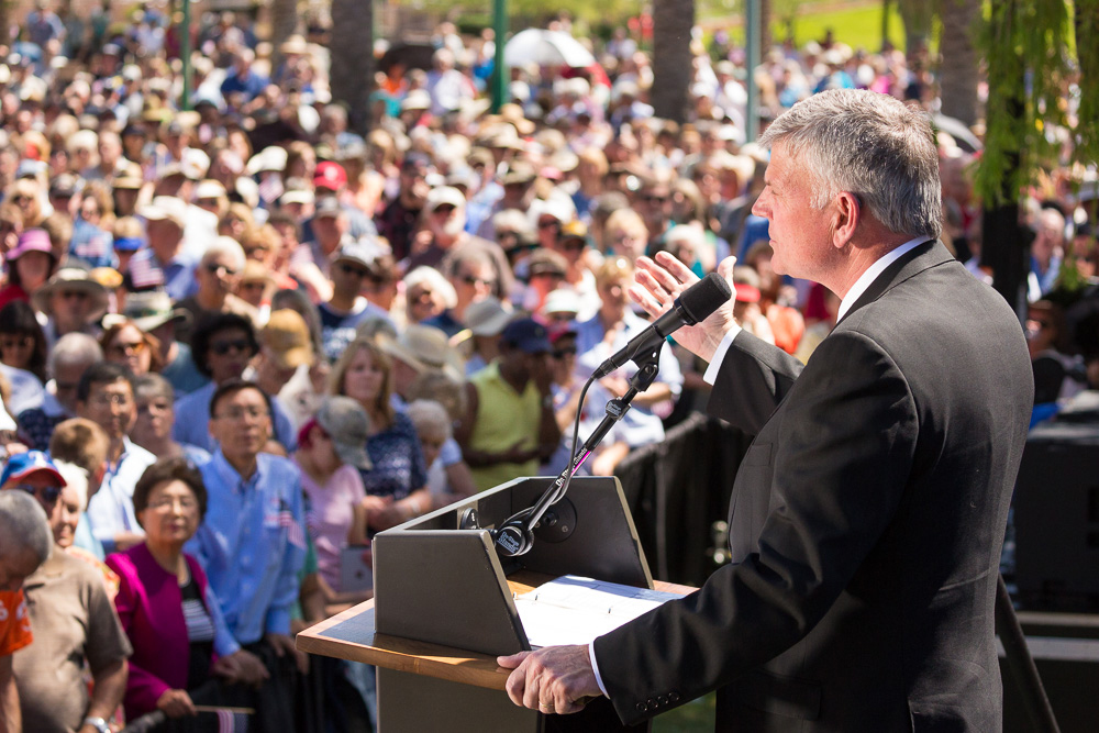 Franklin Graham behind podium; crowd in background