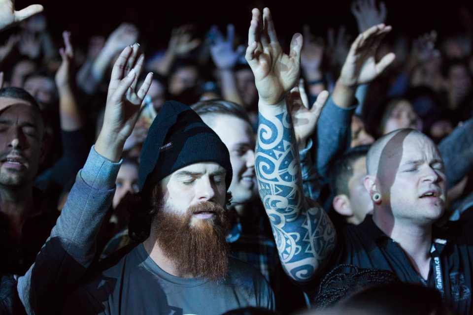 tattooed men with hands raised
