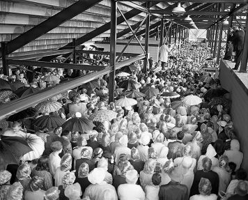 Billy Graham standing on stage under bleachers; people with umbrellas