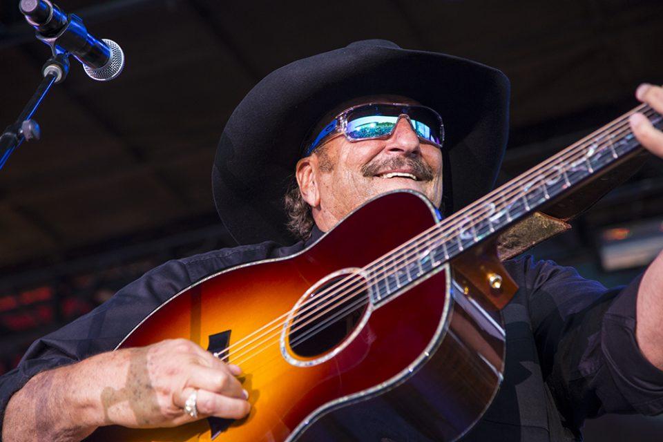 Dennis Agajanian smiling, playing guitar