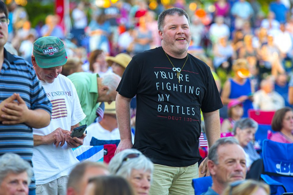 "man wearing ""you fight my battles"" shirt"