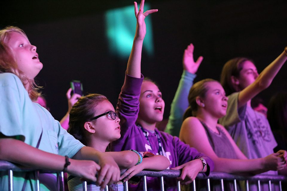 Kids singing along to worship songs with arms raised