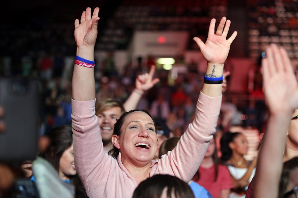 Woman with arms lifted in worship during The Afters performance