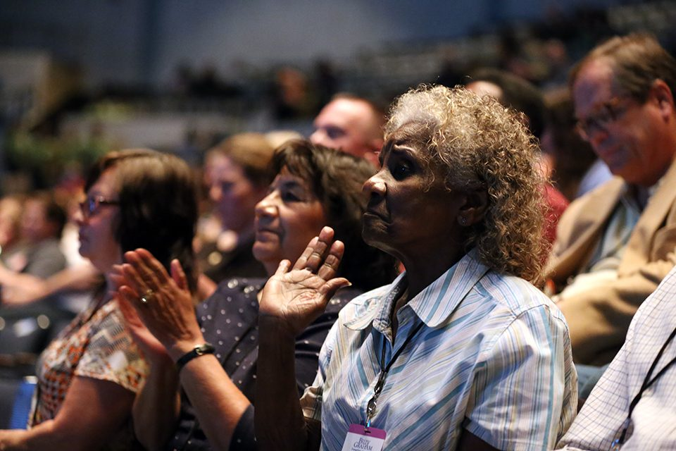 Older women clapping, hand raised in worship
