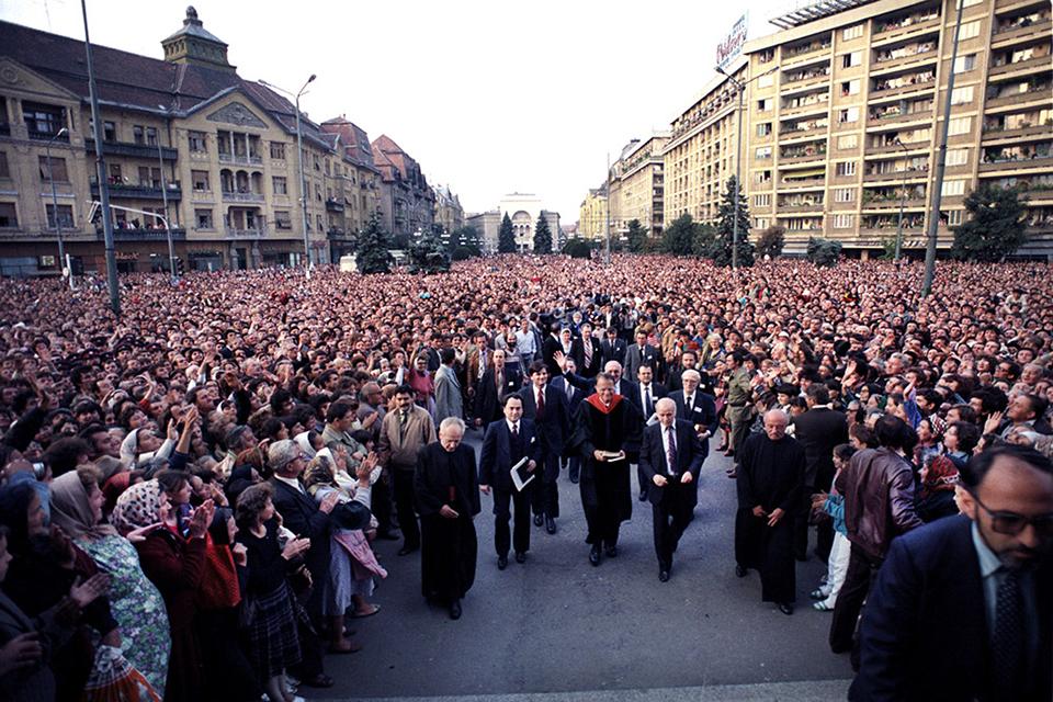 Billy Graham walking through street in Romania, large crowd gathered around