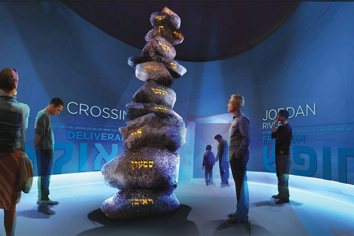 Visitors looking at a tall structure of stones with illuminated writing on the side