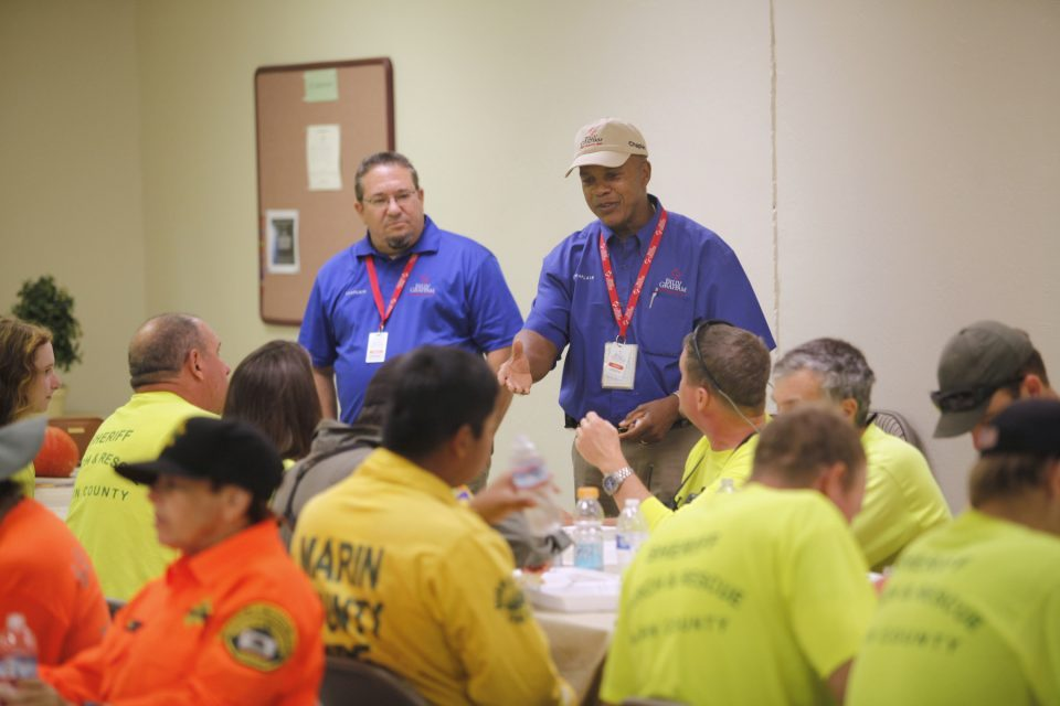 Chaplains addressing first responders during a meal