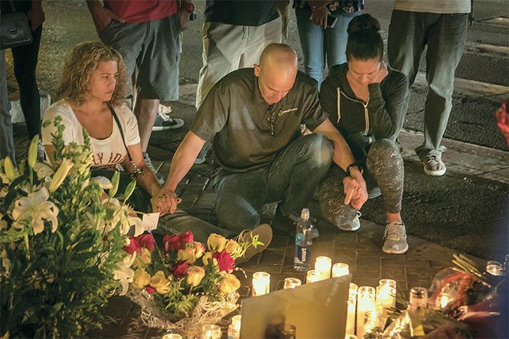 People kneeling, holding hands, praying at Las Vegas memorial for victims