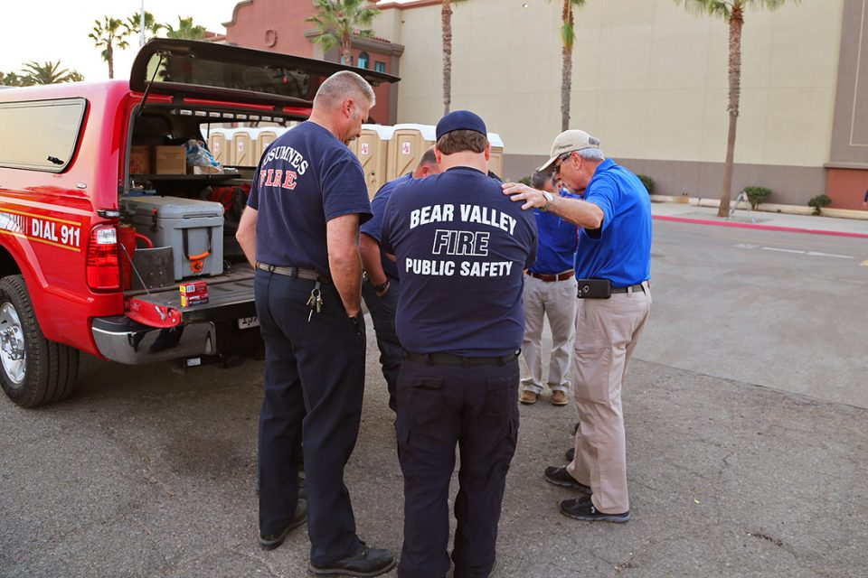 Chaplains pray with firefighters near fire truck