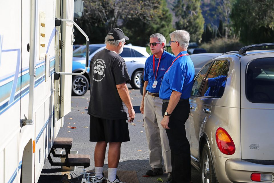 Three men, including two chaplains, stand outside a mobile home, talking