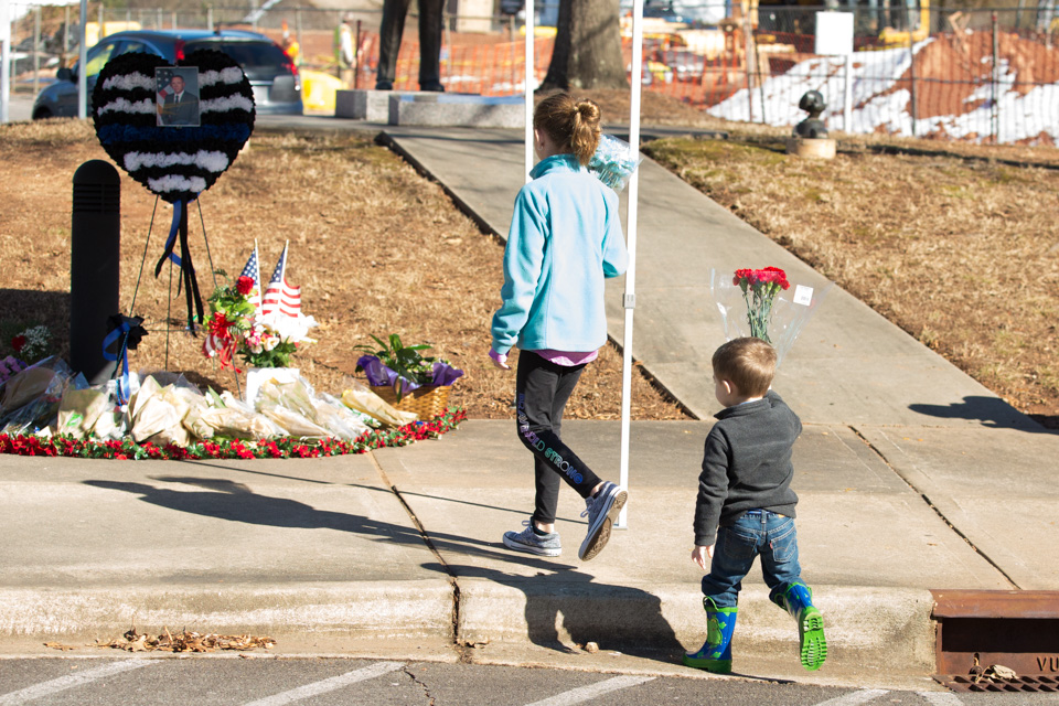 Young boy and girl carry flowers to memorial