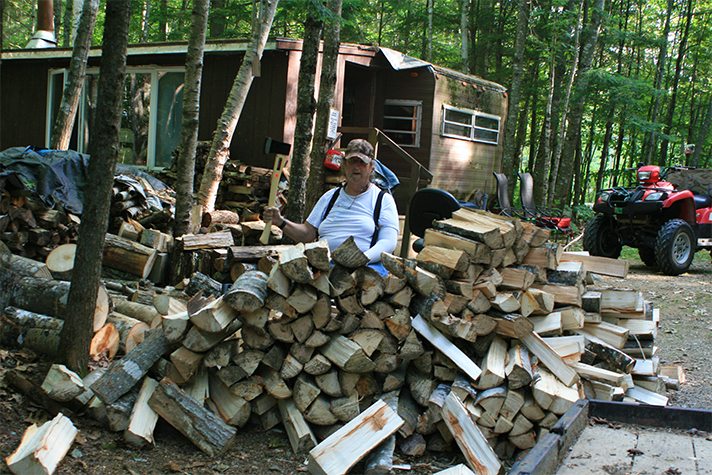 Gary Hand sitting behind woodpile