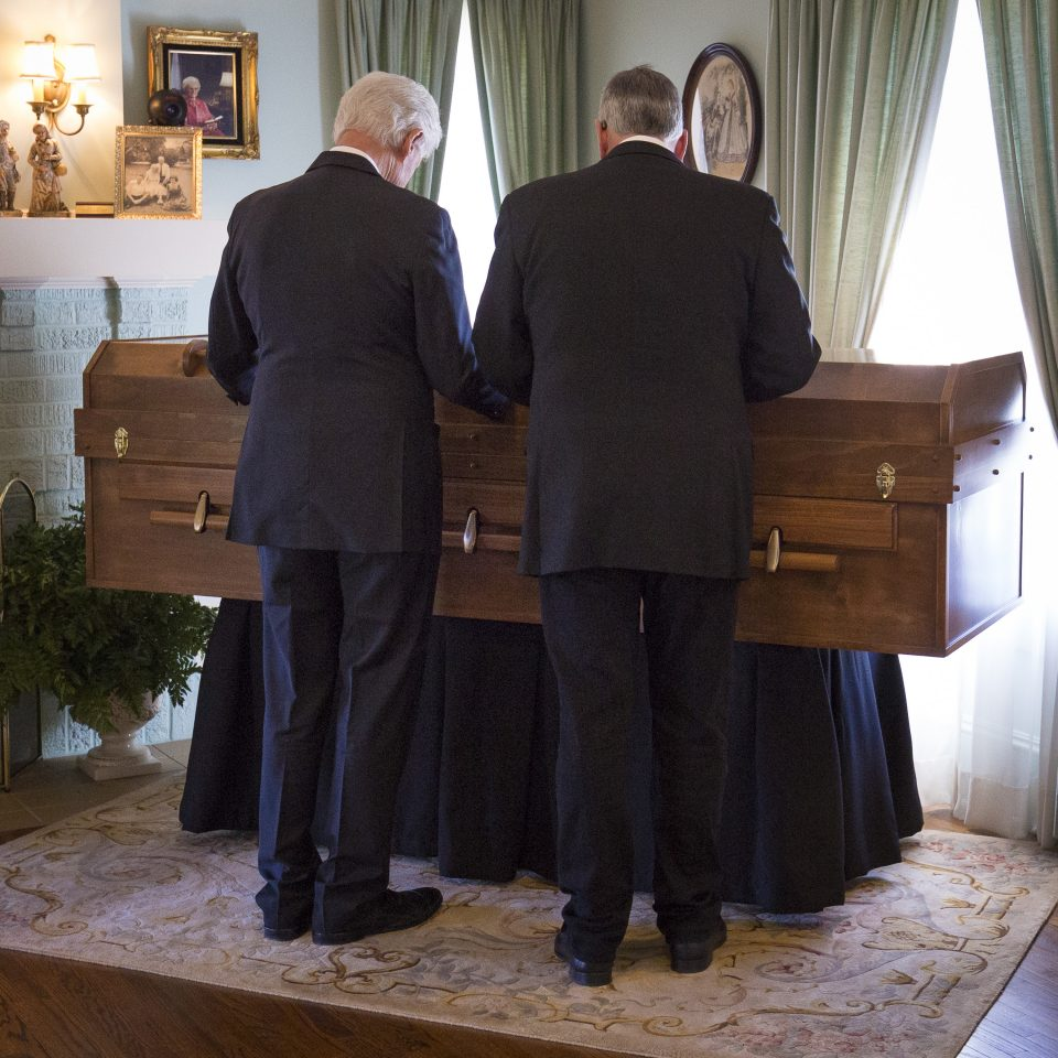 President Clinton and Franklin Graham pray over Billy Graham's casket