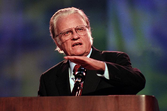 Billy Graham preaching behind podium