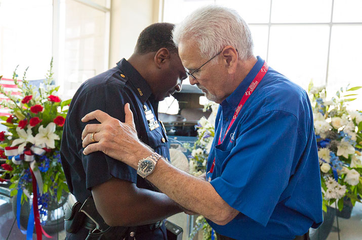 chaplain prays with police officer