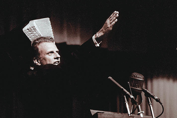 Billy Graham preaching and holding up Bible and hand