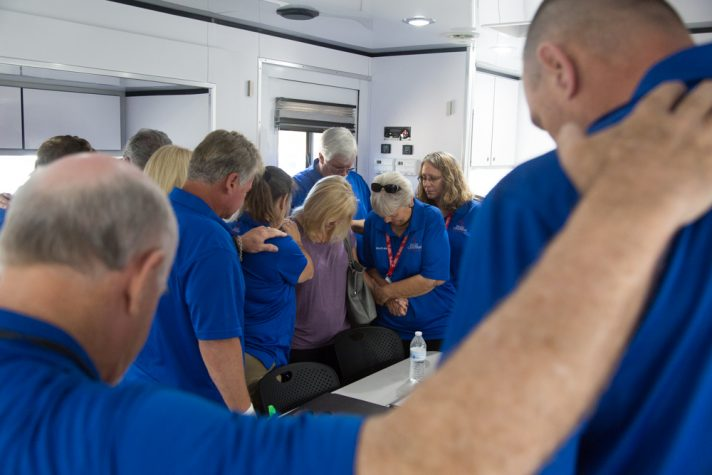 Chaplains in blue shirts huddled around woman in prayer