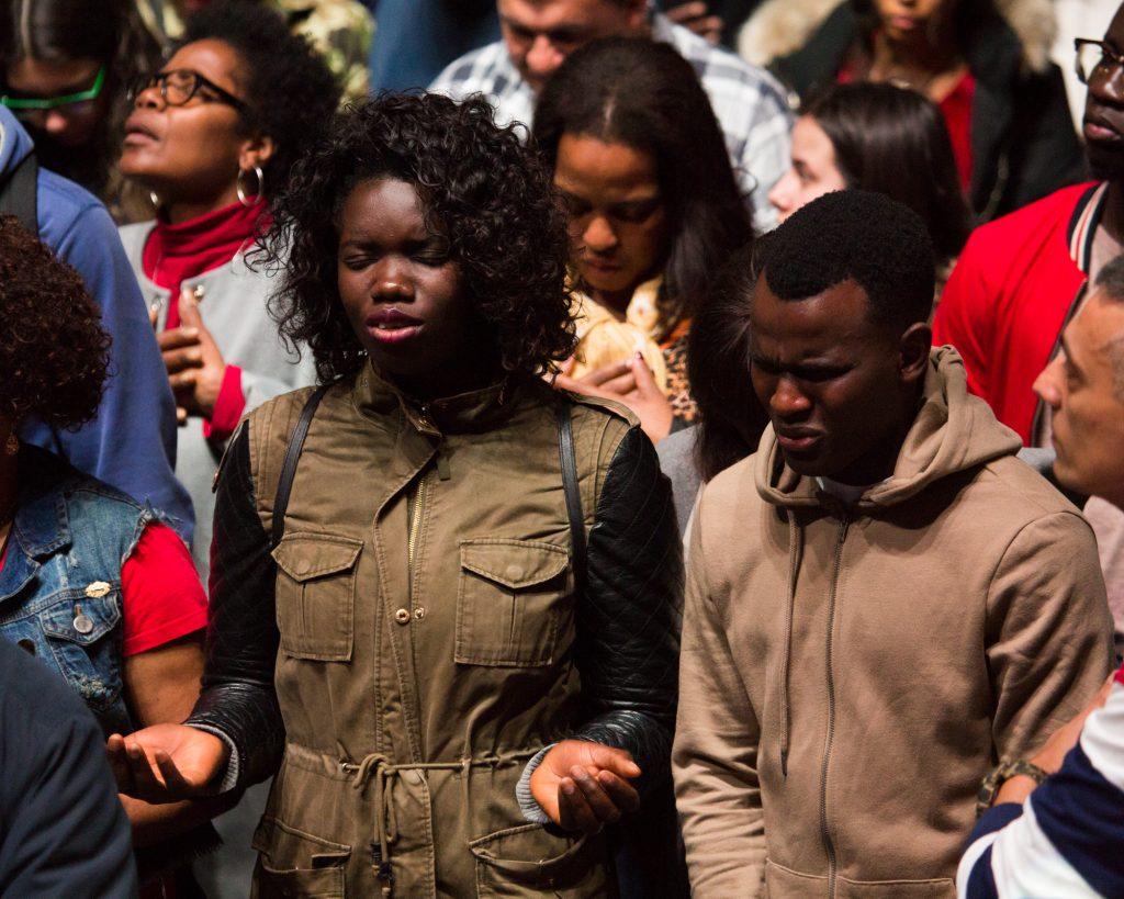 Woman and man praying in crowd