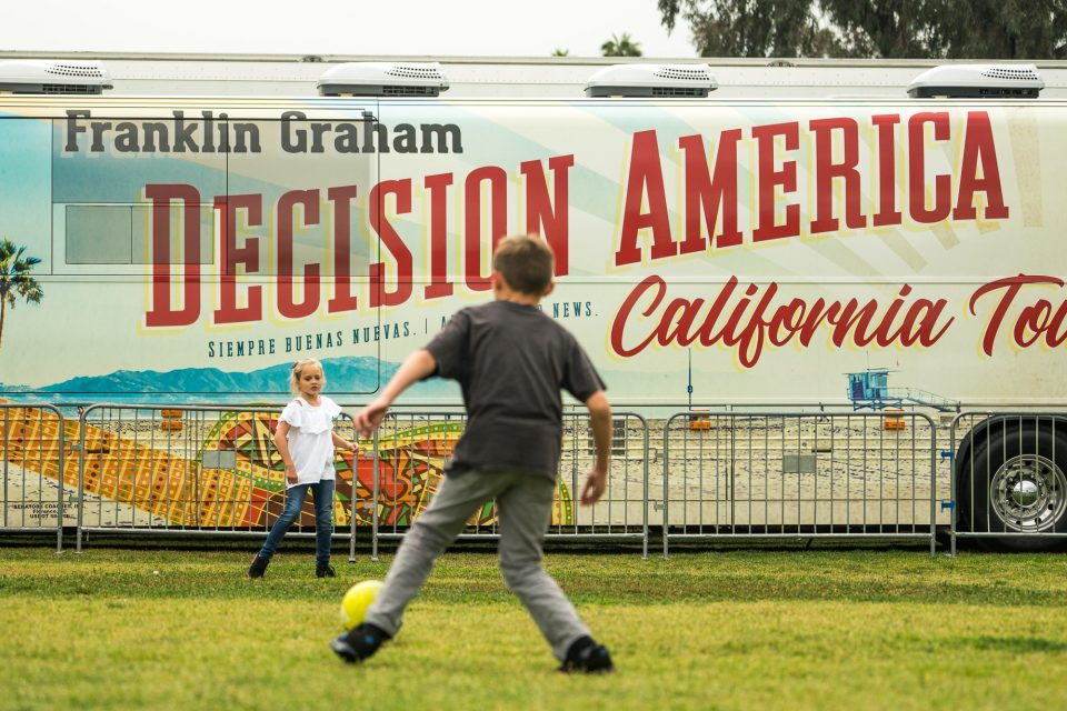 Kids kicking a soccer ball in front of Decision America California Tour bus