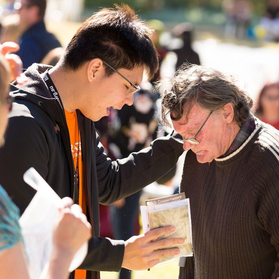 Prayer volunteer prays with man