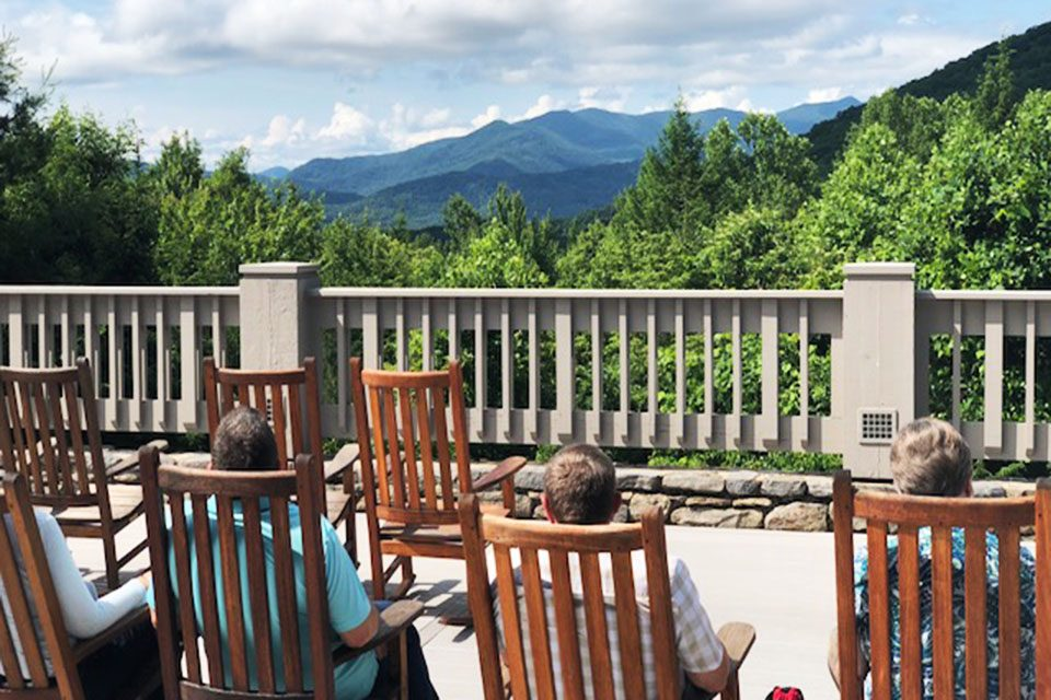 Chaplains in rocking chairs facing the mountains.