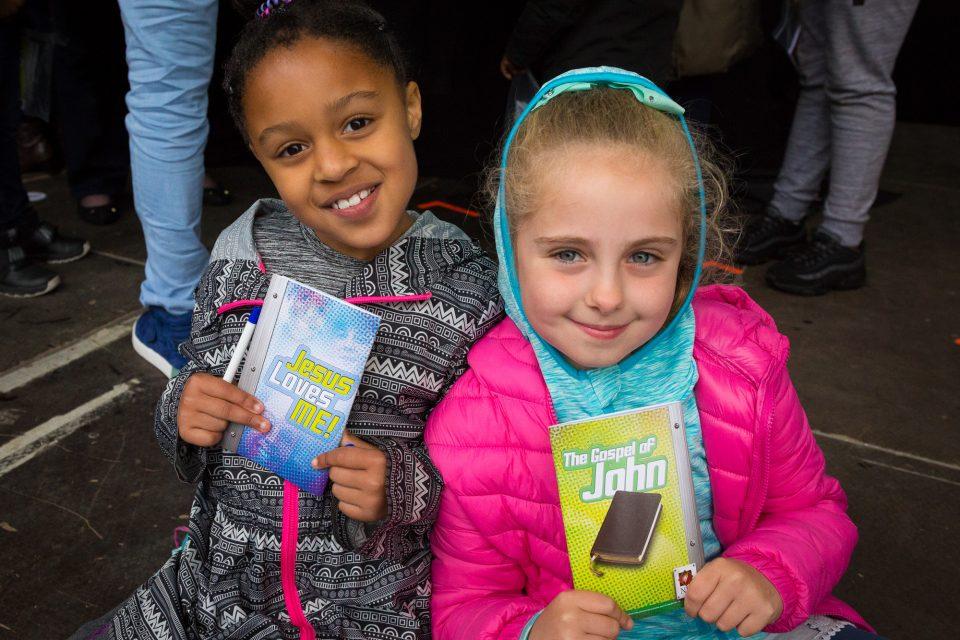 Two little girls holding KidzFest materials