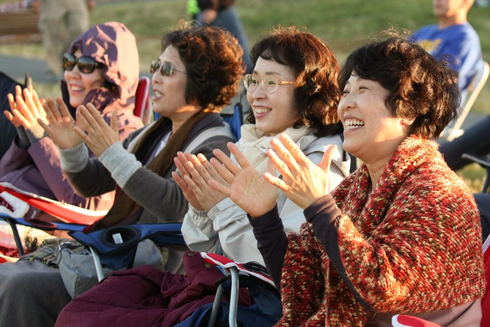 Several Asian women smile and clap hands