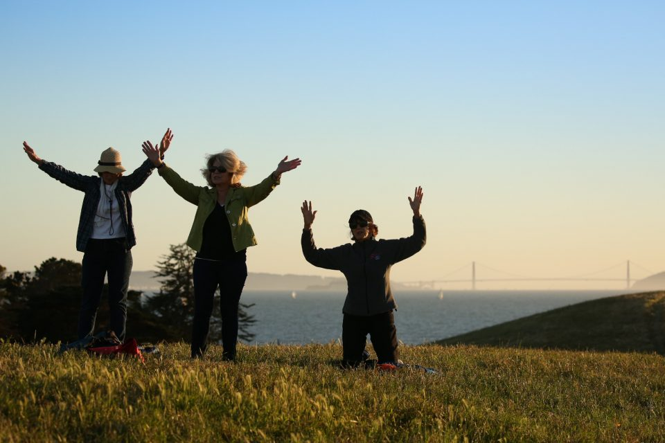 3 women praising God on hillside