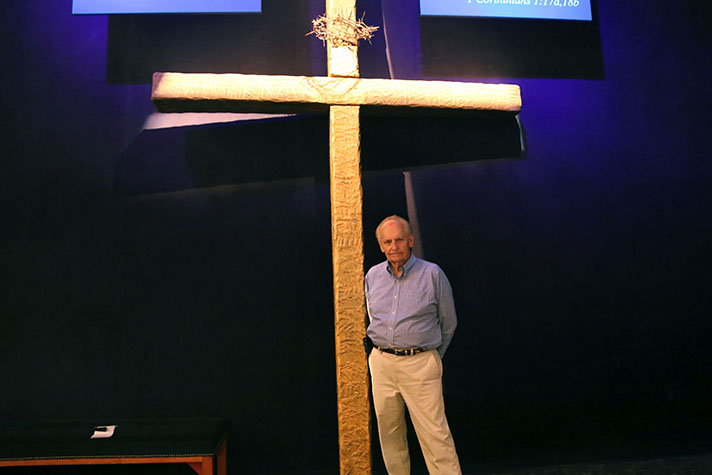 Man standing in front of a cross.