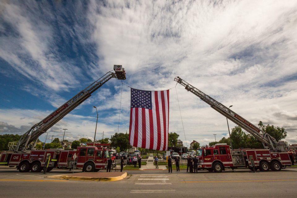 Firetrucks holding up flag