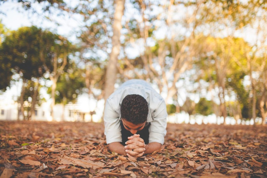 man praying in fall forest