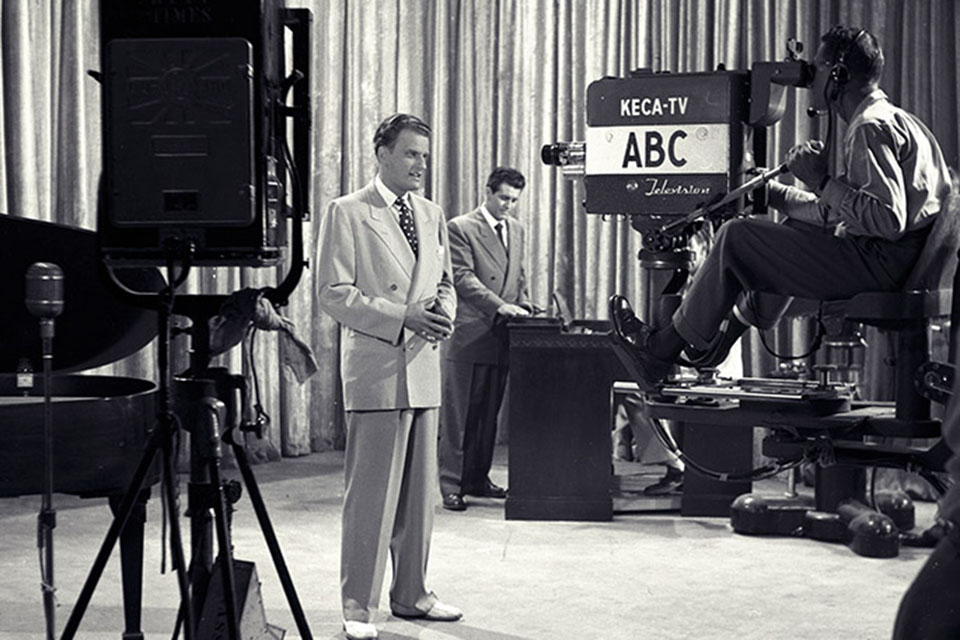 Billy Graham standing in front of an ABC television camera with Cliff Barrows in the background