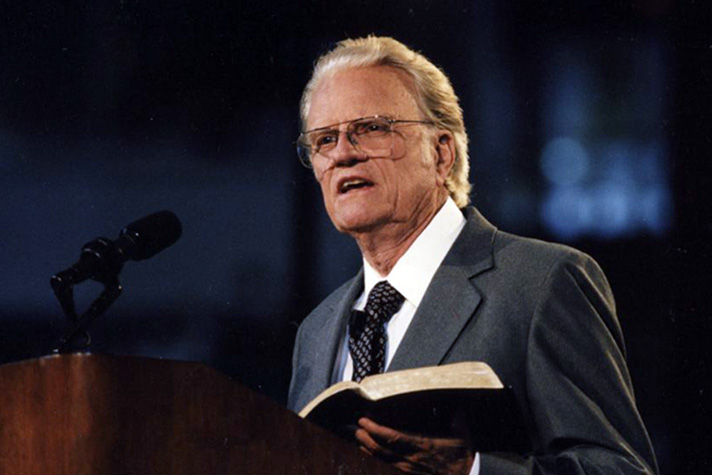 Billy Graham holding Bible at podium