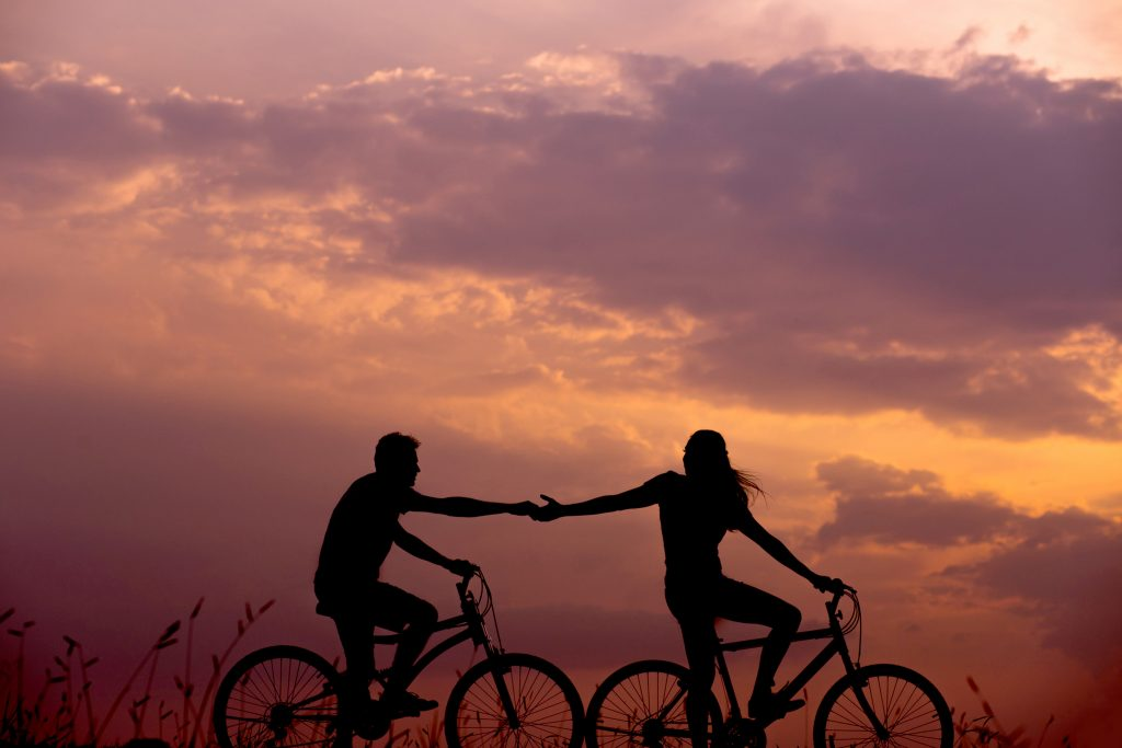 man and woman on separate  bicycles