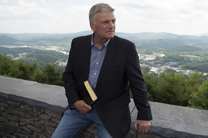 Franklin Graham sitting on stone wall, Bible in hand, looking to side