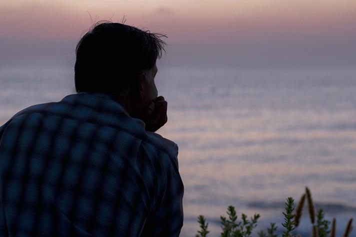 man overlooking ocean