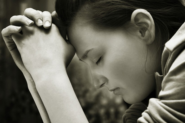 woman head bowed, eyes closed in prayer