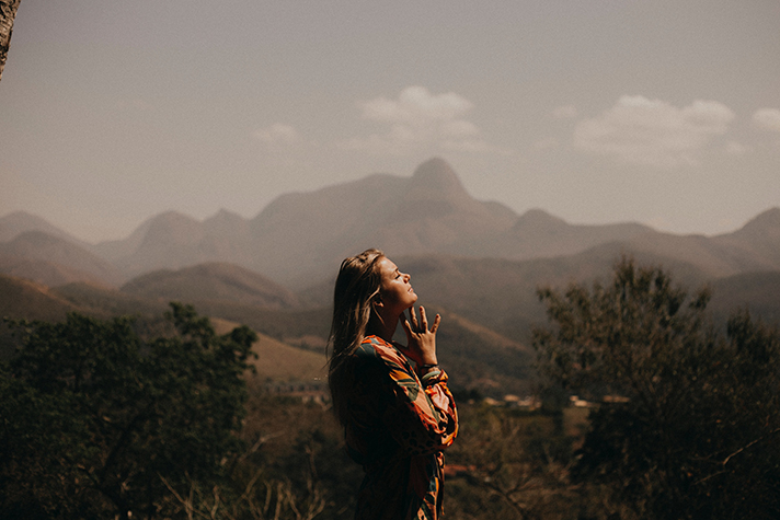 Girl clasping hands in prayer with backdrop of mountains